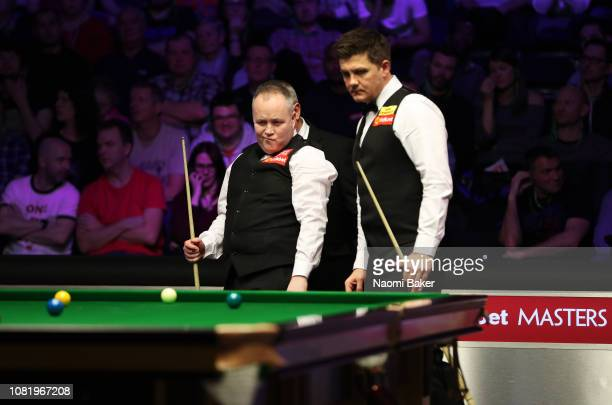 John Higgins of Scotland and Ryan Day of Wales look at the table during their first round match during day one of The Dafabet Masters at Alexandra...