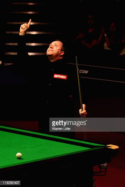 John Higgins of Scotland celebrates beating Mark Williams of Wales in the semi final of the Betfredcom World Snooker Championship at the Crucible...
