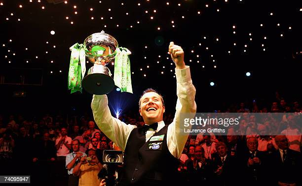 John Higgins of Scotland celebrates victory against Mark Selby of England in the Final of the 888com World Championship at the Crucible Theatre May 7...