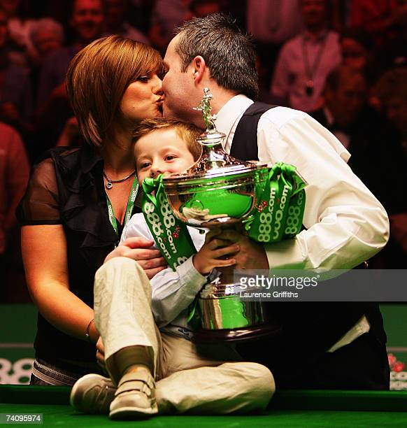 John Higgins of Scotland celebrates victory against Mark Selby of England with his wife Denise and son Pierce in the Final of the 888com World...