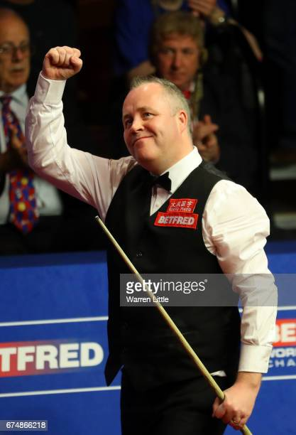 John Higgins of Scotland celebrates winning his semifinal match against Barry Hawkins of England on day fifteen of Betfred World Championship 2017 at...