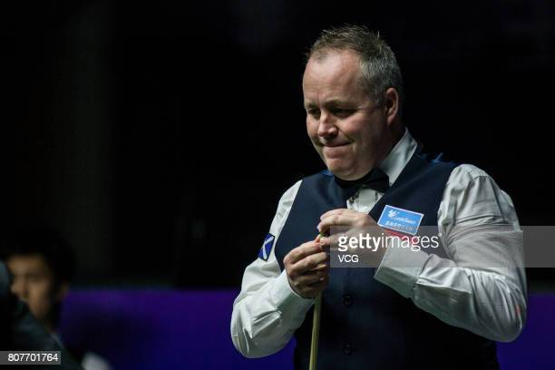 John Higgins of Scotland chalks the cue against Thepchaiya UnNooh of Thailand and Noppon Saengkham of Thailand on day one of 2017 Snooker World Cup...