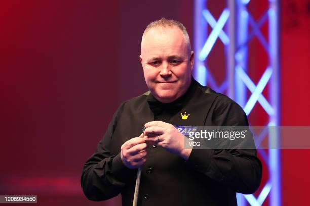 John Higgins of Scotland chalks the cue during a quarter-final match against Judd Trump of England on day three of 2020 Coral Players Championship at...