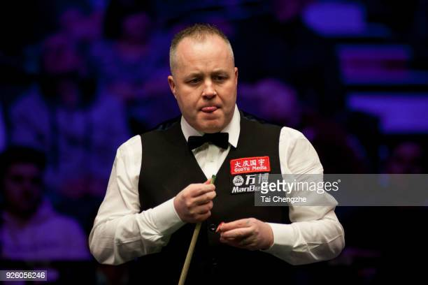 John Higgins of Scotland chalks the cue during his fourth round match against Nigel Bond of England on day four of 2018 ManBetX Welsh Open at...