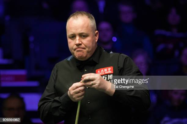 John Higgins of Scotland chalks the cue during his quarterfinal match against Ronnie O'Sullivan of England on day five of 2018 ManBetX Welsh Open at...