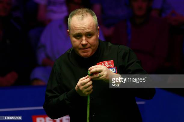 John Higgins of Scotland chalks the cue in the semifinal match against David Gilbert of England on day fourteen of the 2019 Betfred World Snooker...