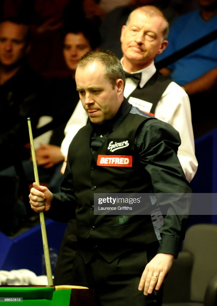 John Higgins of Scotland eyes up a shot in front of Steve Davis of England during the Betfred.com World Snooker Championships match at The Crucible Theatre on April 23, 2010 in Sheffield, England.