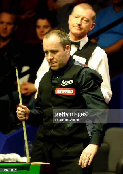 John Higgins of Scotland eyes up a shot in front of Steve Davis of England during the Betfredcom World Snooker Championships match at The Crucible...