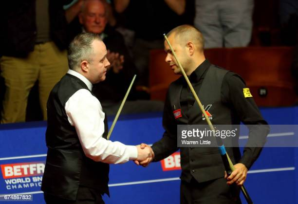 John Higgins of Scotland is congratulated by Barry Hawkins of England after winning their semi final match on day fifteen of Betfred World...