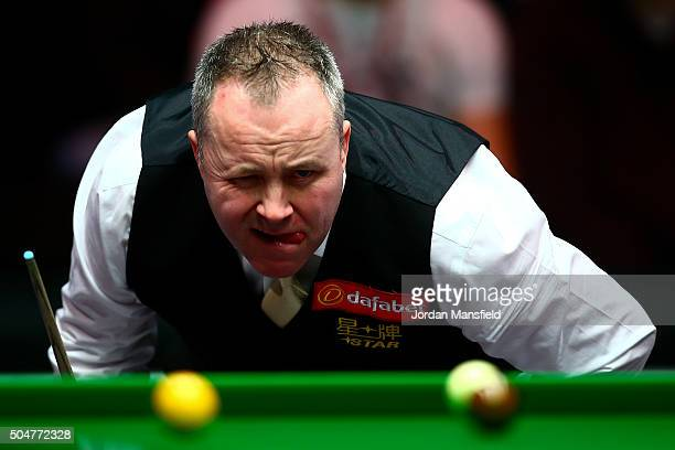 John Higgins of Scotland lines up a shot in his first round match against Liang Wenbo of China during Day Four of the Dafabet Masters at Alexandra...