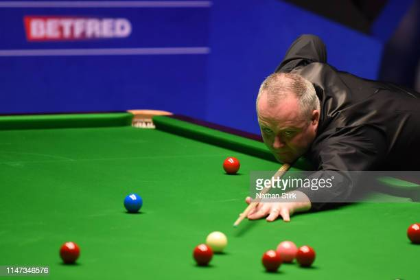 John Higgins of Scotland plays a shot during day 17 of the 2019 Betfred World Snooker Championship final between John Higgins and Judd Trump at...