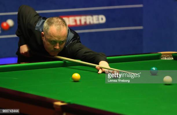 John Higgins of Scotland plays a shot during the fourth session of the final against Mark Williams of Wales during day seventeen of World Snooker...