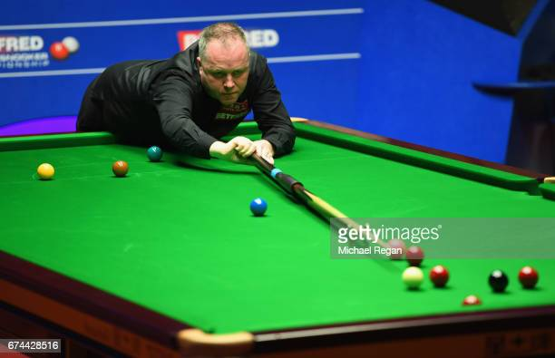 John Higgins of Scotland plays a shot during the semifinal match against Barry Hawkins of England on day fourteen of Betfred World Championship 2017...