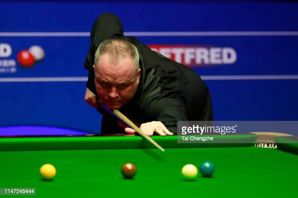 John Higgins of Scotland plays a shot in the final match against Judd Trump of England on day 16 of the 2019 Betfred World Snooker Championship at...