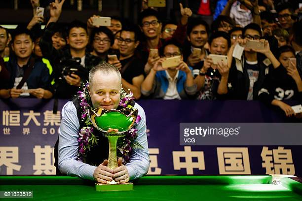 John Higgins of Scotland poses with his trophy after winning Stuart Bingham of England in the final match on Day five of Evergrande China...