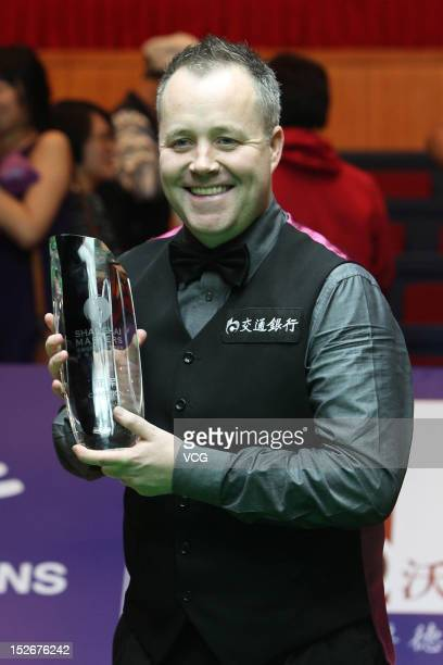 John Higgins of Scotland poses with the trophy after winning the final match against Judd Trump of England on day seven of the 2012 World Snooker...