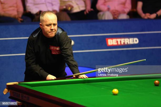 John Higgins of Scotland prepares to play his shot during his semifinals match against Kyren Wilson of England during day fifteen of World Snooker...