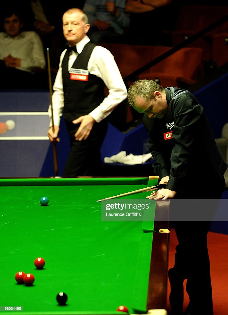 John Higgins of Scotland reflects on a missed red in front of Steve Davis of England during the Betfred.com World Snooker Championships match at The Crucible Theatre on April 23, 2010 in Sheffield, England.