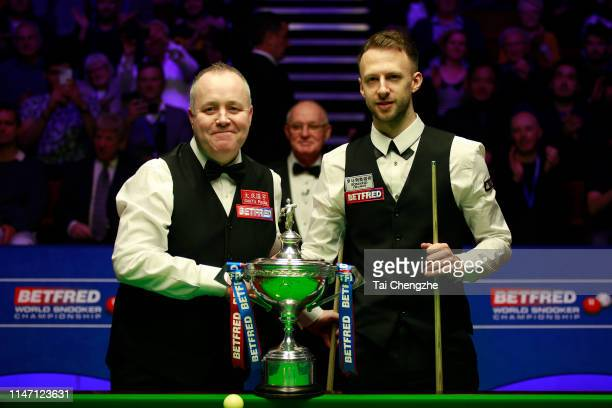 John Higgins of Scotland shakes hands with Judd Trump of England prior to their final match on day 16 of the 2019 Betfred World Snooker Championship...