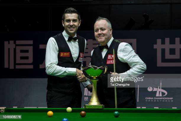 John Higgins of Scotland shakes hands with Mark Selby of England prior to their final match during day seven of the Evergrande 2018 World Snooker...