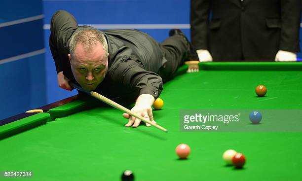 John Higgins plays a shot against Ryan Day during their first round match of the World Snooker Championship at Crucible Theatre on April 19 2016 in...