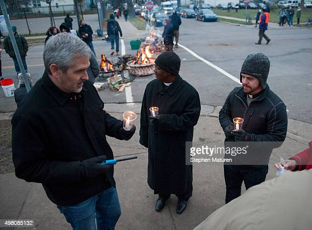 C John Hildebrand Priest James N Wilson II and Pastor Jay Carlson light candles before a candlelight vigil held for Jamar Clark outside the 4th...