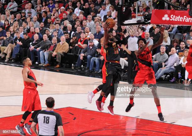 John Holland of the Cleveland Cavaliers dunks against Ed Davis of the Portland Trail Blazers on March 15 2018 at the Moda Center Arena in Portland...