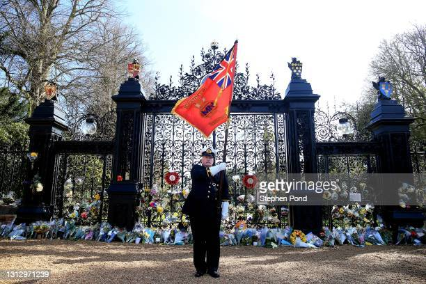 John Houston, formerly of the Merchant Navy, and now flag bearer for the local British Legion, lowers his flag as he pauses for a period of silence...