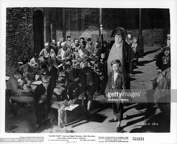 John Howard Davies walking to front of the room in a scene from the film 'Oliver Twist', 1948.