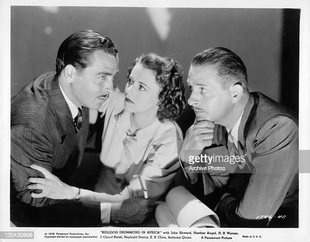 John Howard is held by Heather Angel while Reginald Denny watches in a scene from the film 'Bulldog Drummond in Africa' 1938