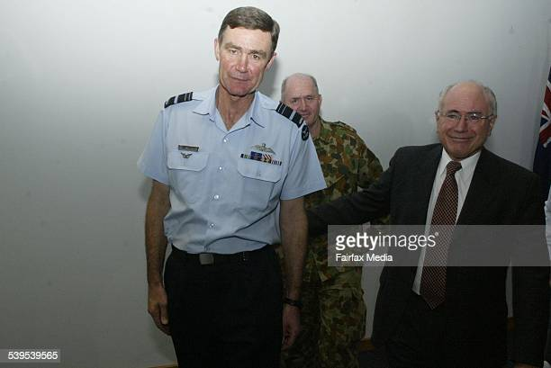 PM John Howard with new defence force Chief Air Vice Marshall Angus Houston and outgoing Chief General Peter Cosgrove at Robertson Barracks on the...