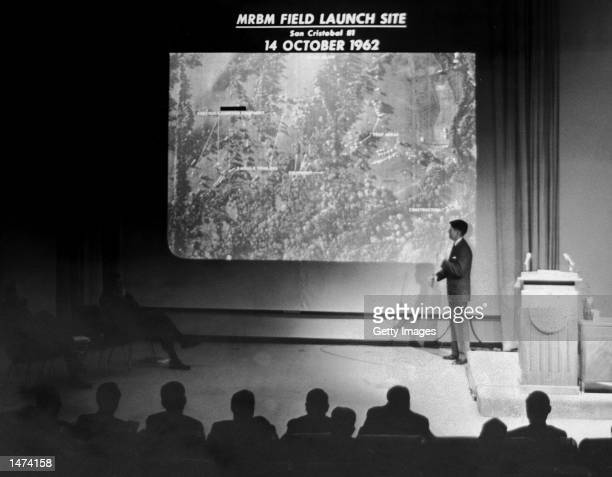 John Hughes, Special Assistant to the Director of Defense Intelligence, conducts a military briefing for the news media showing the absence of Soviet...