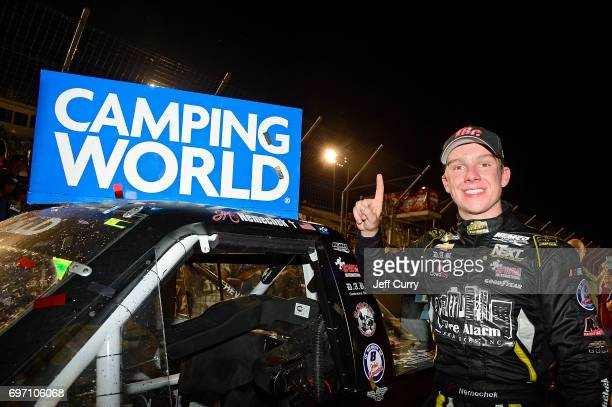 John Hunter Nemechek driver of the Chevrolet Silverado places the winner's decal on the truck in Victory Lane after winning the NASCAR Camping World...