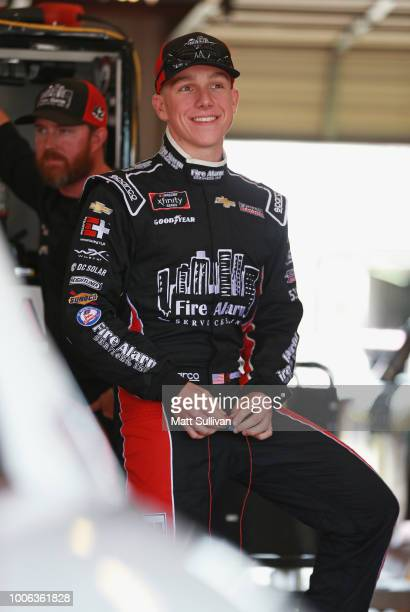 John Hunter Nemechek driver of the Fire Alarm Services Inc Chevrolet stands by his car during practice for the NASCAR Xfinity Series US Cellular 250...