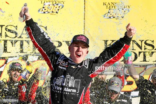 John Hunter Nemechek driver of the Fire Alarm Services Inc Chevrolet celebrates in Victory Lane after winning the NASCAR Xfinity Series Kansas...