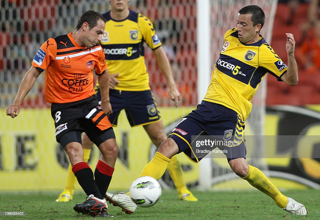 John Hutchinson of the Mariners and Massimo Murdocca of the Roar compete for the ball during the round 11 A-League match between the Brisbane Roar and the Central Coast Mariners at Suncorp Stadium on December 17, 2011 in Brisbane, Australia.