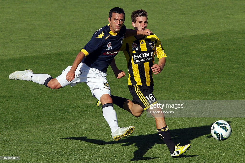 John Hutchinson of the Mariners shoots while Louis Fenton of the Phoenix looks on during the round 12 A-League match between the Wellington Phoenix and the Central Coast Mariners at Westpac Stadium on December 22, 2012 in Wellington, New Zealand.