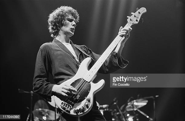 John Illsley bassist with Dire Straits playing the bass guitar on stage during a live concert performance by the band at Wembley Arena in London...