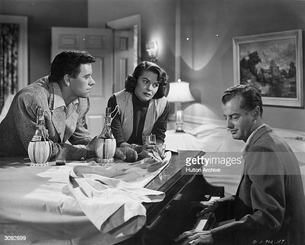 John Ireland and Joanne Dru listen to Shepperd Strudwick playing the piano in a scene from the political drama 'All The King's Men' based on the life...