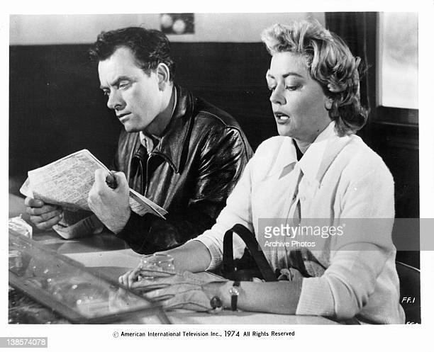 John Ireland reading newspaper next to Dorothy Malone in a scene from the film 'The Fast And Furious' 1955