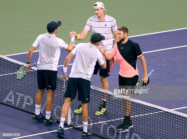 John Isner and Jack Sock of the United States shake hands with Bob Bryan and Mike Bryan of the United States after beating them in the ATP doubles...
