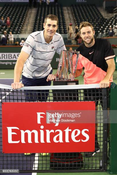 John Isner and Jack Sock pose with the winner's trophy after defeating Mike Bryan and Bob Bryan during the men's doubles final on Day 13 of the BNP...