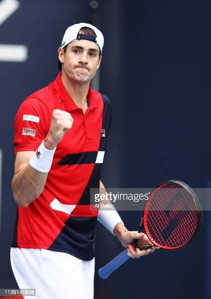 John Isner celebrates a point against Felix Auger Aliassime of Canada during day 12 of the Miami Open presented by Itau at Hard Rock Stadium on March...