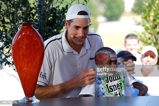 John Isner is interviewed with his selfproclaimed No 1 fan Justin Roberts after defeating Marcos Baghdatis of Cyprus during the BBT Atlanta Open...