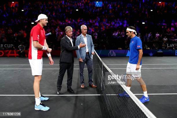 John Isner of Team World and Roger Federer of Team Europe take part in the coin toss with former tennis player Todd Martin prior to their singles...