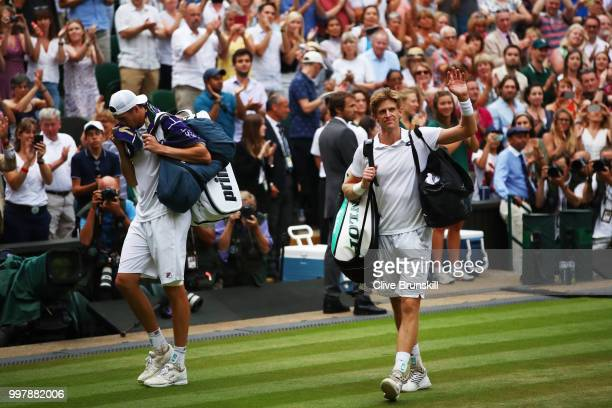John Isner of The United States and Kevin Anderson of South Africa leave Centre Court after their Men's Singles semifinal match on day eleven of the...