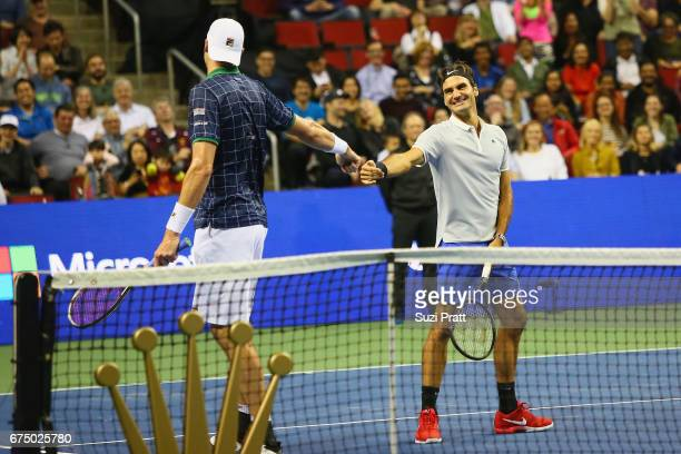 John Isner of the United States high fives Roger Federer of Switzerland at the Match For Africa 4 exhibition match at KeyArena on April 29, 2017 in...