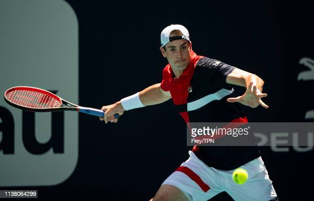 John Isner of the United States hits a forehand against Albert RamosVinolas of Spain in the third round of the men's singles in the Miami Open at the...