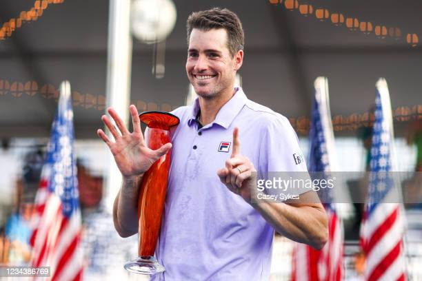 John Isner of the United States holds up six fingers, signifiying his six Atlanta Open victories, while holding the winners trophy after winning the...