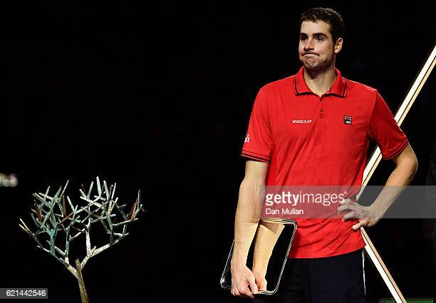 John Isner of the United States looks at the 'Tree of Fanti' trophy after loosing to Andy Murray of Great Britain in the Mens Singles Final on day...